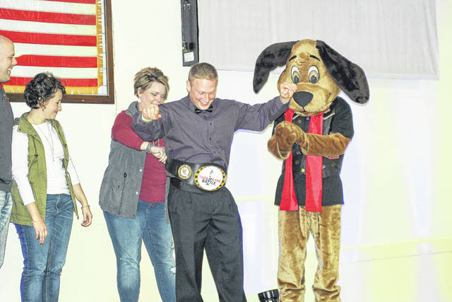 Shelby County Sheriff's Deputy Joel March receives the champion's belt at the conclusion of the SCARF Lip Sync Battle Saturday night at the Sidney American Legion. March raised $3,311.50 for SCARF. The evening raised $13,779.44 for the organization.