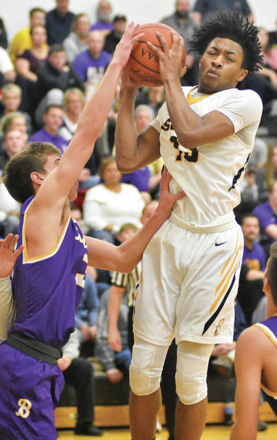 Sidney junior forward Ratez Roberts shoots with pressure from Butler's Michael Kreill during a Greater Western Ohio Conference game on Tuesday in Sidney.
