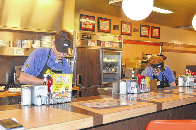 Gabby Schellenberg and Cody Kanther clean and prepare for incoming customers at the Waffle House in Wapakoneta. Camri Nelson | The Lima News