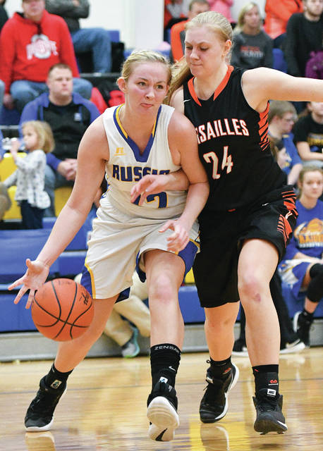 Versailles junior forward Elizabeth Ording gets tangled up with Russia's Cameo Wilson during a nonconference game last Saturday. Russia plays at Fort Loramie on Saturday.