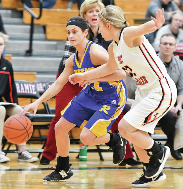 Russia's Whitney Pleiman dribbles with pressure from Fort Loramie's Kenzie Hoelscher during a Shelby County Athletic League game on Saturday.
