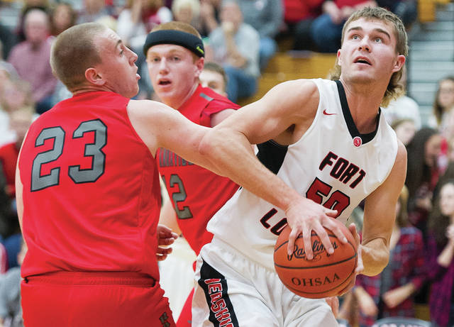 Fort Loramie's Tyler Siegel looks to shoot with pressure from New Knoxville's Nathan Tinnerman during a nonconference game on Dec. 2. The Redskins are ranked No. 1 in Division IV in the Associated Press state poll.   Bryant Billing | Sidney Daily News