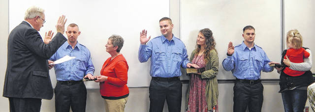 Three new Sidney firefighters were sworn-in on Tuesday, Jan. 16, by Mayor Mike Barhorst at the Nancy Adams Training Center located within Sidney Fire Department's Station 1. Pictured, left to right is Barhorst, Lucas Woodward, with his mother, Cindy Woodward, by his side, Jordan Stemen, with his wife, Haleigh Stemen, by his side, and Mitchell Ahlers, with his wife, Morgan Ahlers, and their young daughter, Isabella, by his side, at the swearing-in ceremony held on their first day on the job.