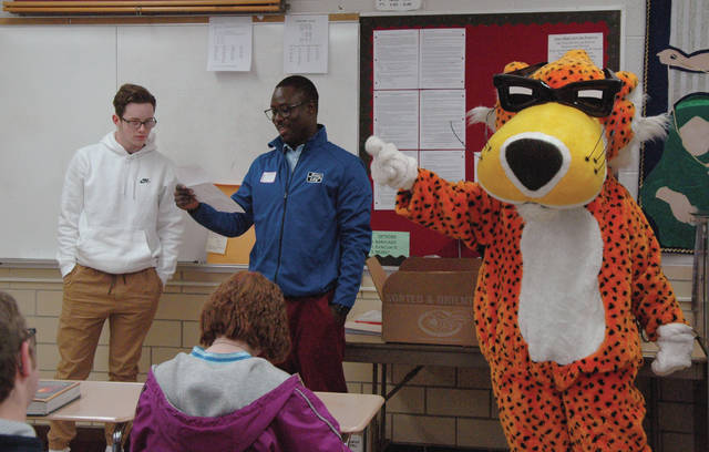 Noah Dimel, 16, of Troy, is presented a thank-you letter and free samples of Baked Cheetos from Frito-Lay by District Sales Manager Mourtada Sakho and Chester Cheetah, Thursday, at Troy High School.