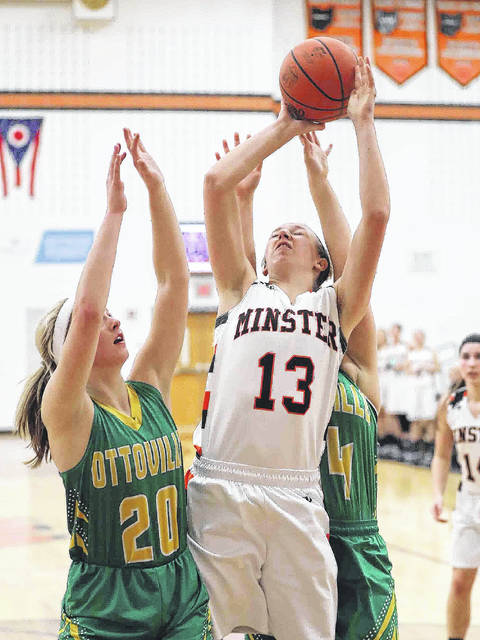 Minster's Paige Thobe puts up a shot againstr Ottoville's Quinley Schlagbaum, left, and Abi Hilvers (right) during Saturday's game at Minster.
