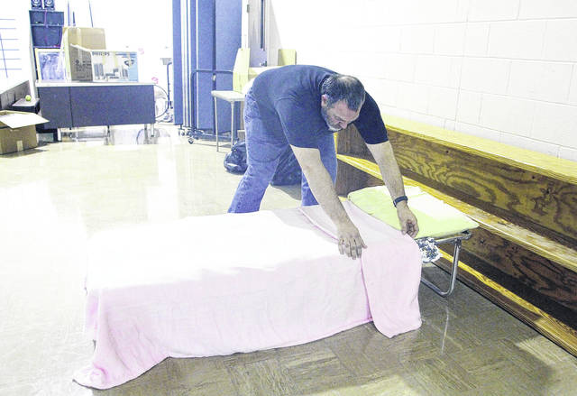 Lt. Joseph Hansen, of Sidney, puts covers on a cot at the Sidney Salvation Army Warming Center Wednesday, Jan. 3. People can enter the warming shelter from 6:30 p.m. until it is locked at 9 p.m. The doors will not be monitored, so once they are closed no one will be able to be let in. Anyone staying at the center will need to be out of the building by 7 a.m. The warming center plans to be open until the end of March. The Salvation Army and its warming center is located at 419 N. Buckeye Ave. Volunteers are needed.
