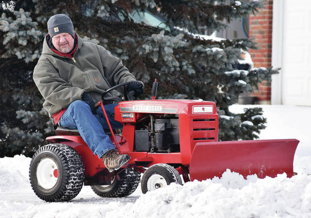 Ron Barhorst, of Fort Loramie, uses a vintage 1969 mini tractor to plow snow from his driveway recently. Barhorst restored the tractor one and a half year ago. Barhorst has two other mini tractors.