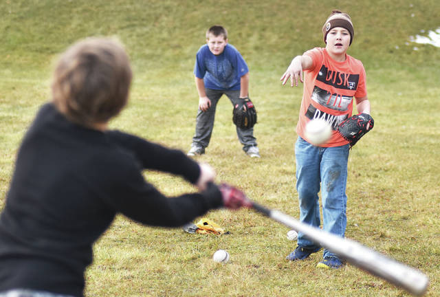 """Taking turns hitting baseballs at McMillen Park Wednesday, Jan. 10, are, left to right, Dallas Carr, 9, and his brother Justin Fent, 10, both the children of Kasey Carr, and Cody Powers, 13, all of Sidney, son of Bill Hughes and Linda Powers. Cody said of three boys """"We play sports a lot. We're athletic."""" The three boys said they play together almost every day regardless of the weather."""