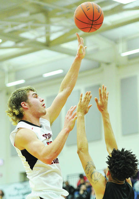 Fort Loramie's Tyler Siegel shoots over Thurgood Marshall's Byron Lanier during a game in Flyin' to the Hoop at Trent Arena in Kettering on Monday.