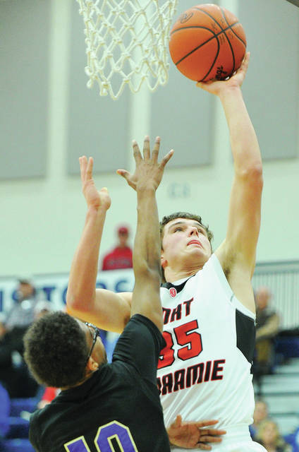 Fort Loramie's Nathan Raterman shoots over Thurgood Marshal's Anthony McCombs at Flyin' to the Hoop at Trent Arena in Kettering on Monday.