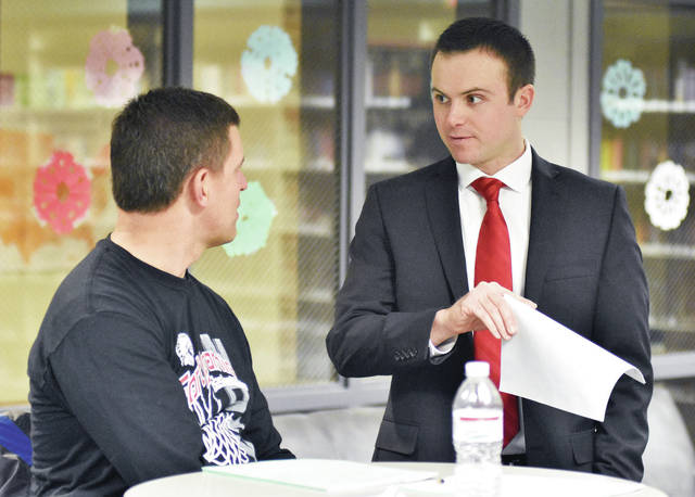New head football coach Spencer Wells, right, of Celina, talks with Fort Loramie Elementary employee Kevin Wrasman during a Fort Loramie School board meeting on Monday, Jan. 15.