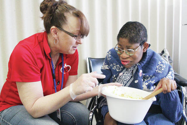 Renea McClosky, left, of Ansonia, helps Brooke Hudson, of Sidney, stir batter for a batch of cookies Wednesday, Jan. 17, during morning activities at Person Centered Services in Sidney. The firm opened Tuesday to provide day services to Shelby County residents with developmental disabilities.