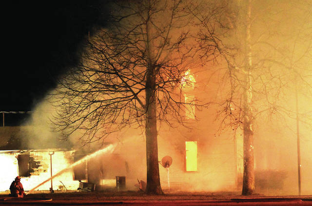 Firefighters battle a house fire at 8418 Fort Loramie-Swanders Road shortly after 6 a.m. Tuesday, Jan. 23. Eight fire departments were dispatched to battle the fire.
