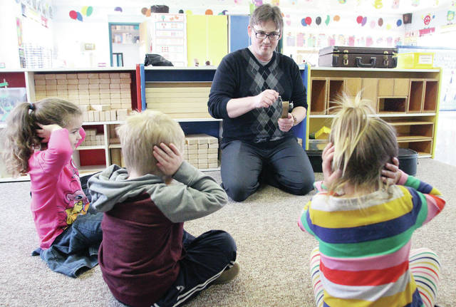 Jackson Center band director Randy Johnson, of Sidney, demonstrates a ratchet to kids at Sidney Cooperative Nursery School Wednesday, Jan. 24. Covering their ears in response to the loud noise created by the ratchet are, left to right, Gabby Snapp, 4, daughter of Lucas and Chandra Snapp, Kayden Wesbecher, 4, son of Aaron and Sarah Wesbecher, and Claire Bucio, 4, all of Sidney, daughter of Chris and Amber Bucio. Johnson came to the nursery school to demonstrate a wide range of musical instruments for the students.