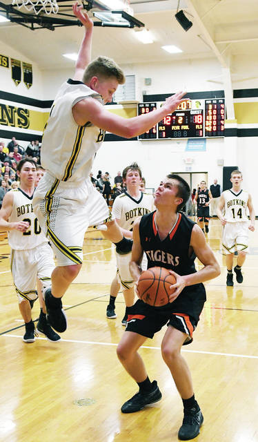 Botkins' Zane Paul jumps as Jackson Center's Calvin Winner looks to shoot during a Shelby County Athletic League game at Botkins on Tuesday.