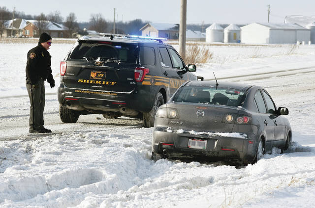 At around 3:30 p.m., Saturday, Dec. 30, a Shelby County Sheriff's Deputy talks with the driver of a car that hit a snowy patch on the 11000 block of state Route 29, causing them to slide into the ditch and become stuck in the deep snow there. Multiple slide-offs were being reported around the area as drivers go over snow and ice covered patches of road.