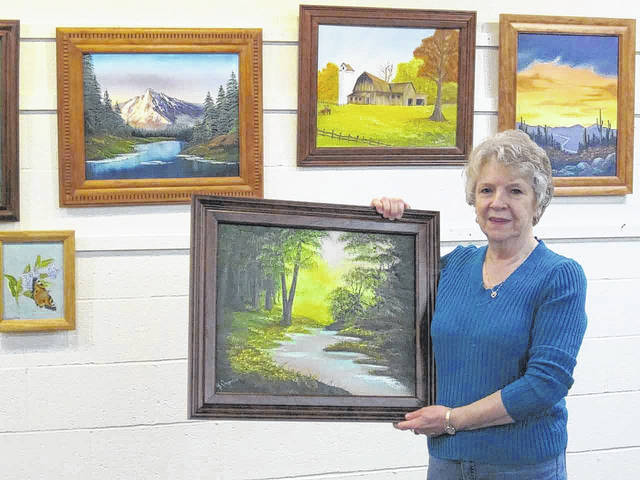 Myra Carpenter, of Sidney, hangs a painting in the Amos Memorial Public Library art gallery in Sidney. An exhibit of her art will continue there through February.