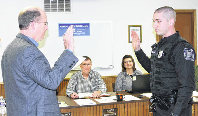 Jackson Center village solicitor Mike Burton, left, administers oath of office to new JC police Officer Zachary M. Smith, right, during Monday night's council meeting, as Mayor Scott Klopfenstein and fiscal officer Bev Wren look on.