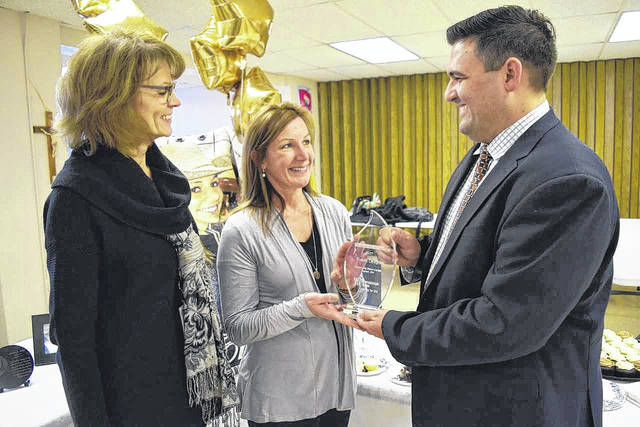Fresenius Kabi representative Anthony Montemurro, right, presents Susan Leugers, middle, with the donation hall of fame award, as Community Blood Center representative Kathy Pleiman, left, looks on.
