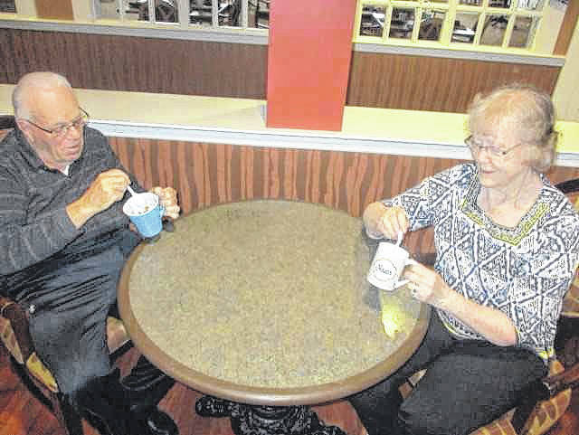 Don Evers, left, and Dorothy Jutte, both of New Bremen, mix up cakes in mugs during a Kitchen Korner activity at Elmwood Assisted Living, recently. To create a peanut butter mug cake, thoroughly mix 3 tablespoons of peanut butter, 1 tablespoon plus 1 teaspoon of sugar and 1 egg in a microwave-safe mug. Microwave for 1 minute.