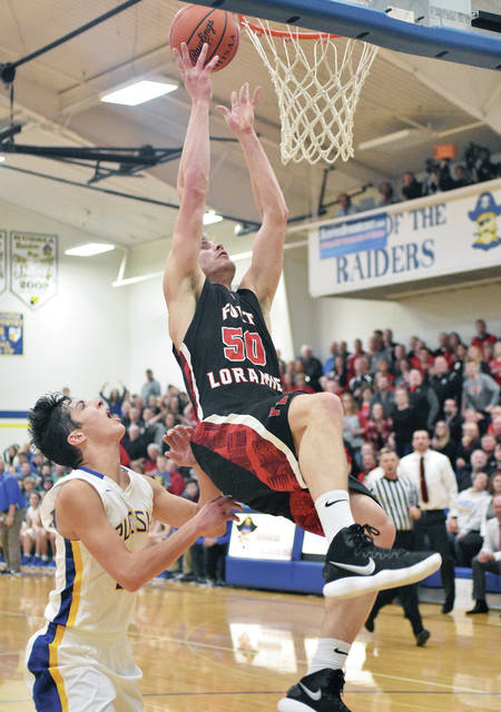 Fort Loramie's Tyler Siegel shoots followed by Russia's Daniel Kearns at Russia. Siegel fell on his back hard during the play.