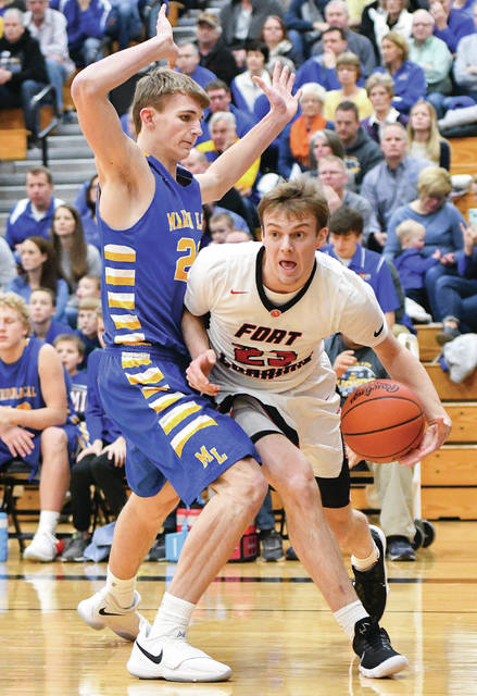 Fort Loramie senior guard Eli Rosengarten drives by Marion Local's Nick Tangeman during a nonconference game on Saturday.