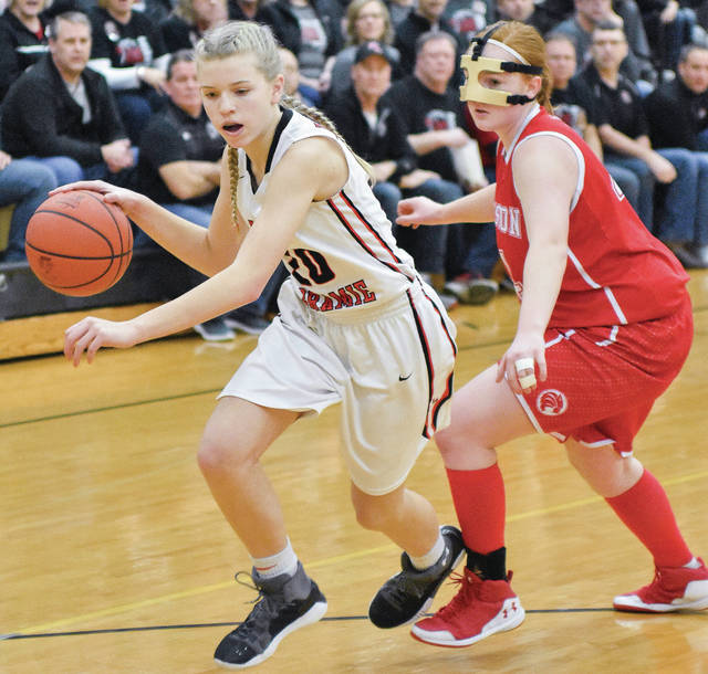 Fort Loramie freshman guard Dana Rose dribbles with pressure from Houston's Rebekah New during a Division IV sectional final on Saturday at Sidney.