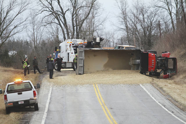 A dump truck sits on its side across state Route 66 south of Newport, Thursday, Feb. 22, following a collision with a trailer of soybeans. The truck's load of 22 tons of gravel covered the road.