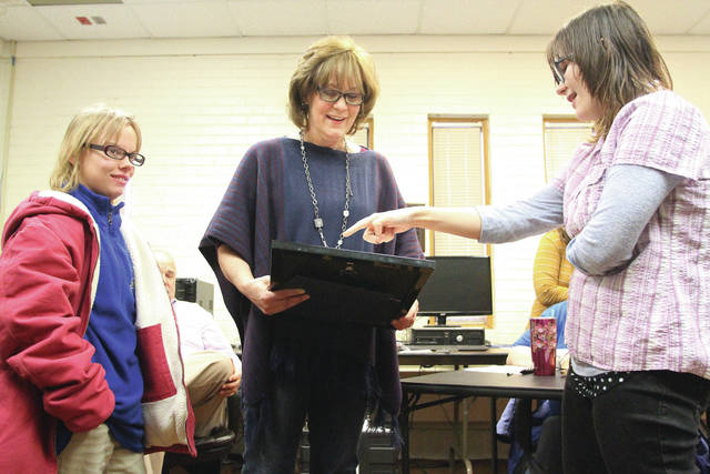 Shelby County Kiwanis Aktion Club members Brittany Meyer, far left, of Fort Loramie, and Melissa Gilmore, far right, of Sidney, present Julie Winner, of Troy, with a framed picture of a tree decorated with fingerprints of all the Aktion Club members. The Aktion Club presented the artwork as a surprise to congratulate Winner on her upcoming retirement.