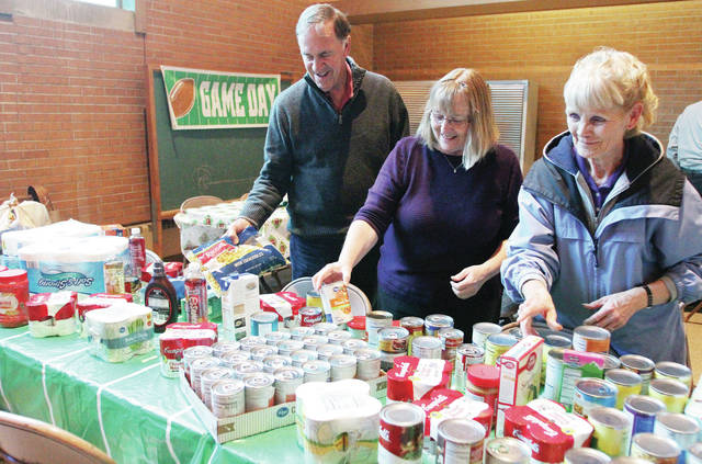 Looking over there donated food items collected during their Souper Bowl Sunday Lunch at Trinity Church of the Brethren are, left to right, Keith Coy, Cathy Clayton, and Darla Jones, all of Sidney. The lunch was held Sunday, Feb. 4. Donated food items will go to the FISH food pantry.