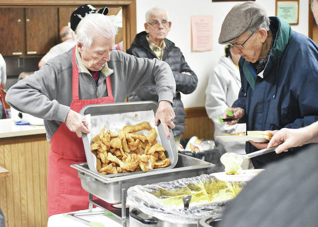 Knights of Columbus member Ron Francis, left, pours out a fresh batch of fried fish as Robert Hilgefort waits to grab another piece at the Knights of Columbus fish fry, Friday, Feb. 9. Both men are from Sidney. Lent begins Wednesday. The Knights will continue weekly Friday fish fries at their hall until Easter.