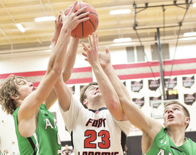 Fort Loramie's Evan Berning is swarmed by Anna's Wyatt Bensman, left, and Riley Huelskamp during a Shelby County Athletic League game at Fort Loramie on Saturday.