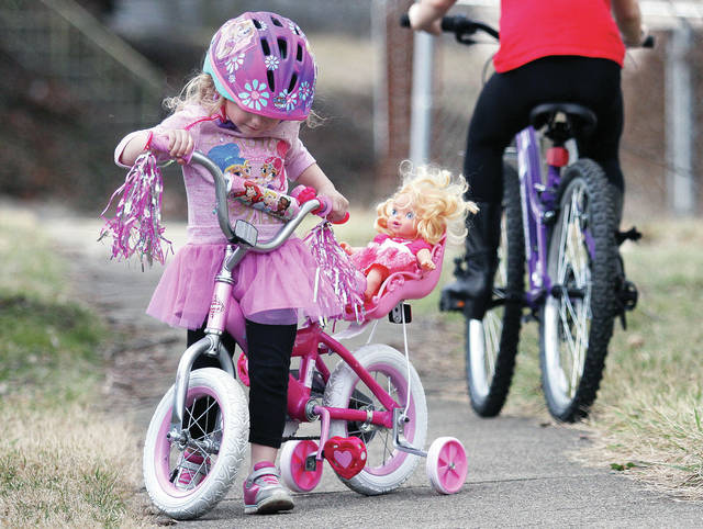 Aurora Williams, left, 4, turns her bike around just off of Fair Road Tuesday, Feb. 20, as her sister Alanna Williams, 10, both of Sidney, daughters of Brooke and Dustin Williams, bikes behind her. Strapped into a child seat on Aurora's bike is her doll she also named Aurora. Aurora's parents got her the bike so she would have a place to seat the dolls she likes. The princess themed bike with heart-shaped pedals is the first bike Aurora has owned.