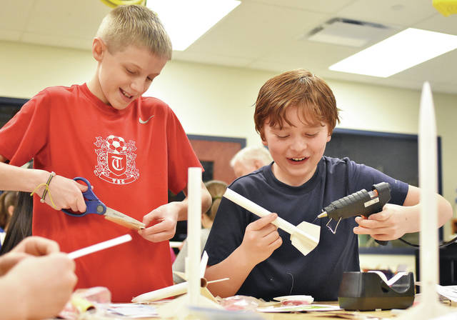Jacob Caldwell, left, 11, of Covington, son of Robin and Brian Caldwell, and Cameron Clark, 11, of Russia, son of Quintina and Dave Leach, assemble model rockets in a Russia Local Schools science class taught by Marcus Petitjean Wednesday, Feb. 21. The class is funded with a grant from the Sidney-Shelby County Chamber of Commerce. The students will eventually launch their rockets. The model rocket project is teaching the students about energy transformation and speed.