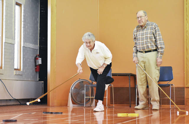 Virginia Hardesty, left, of Uniopolis, plays a friendly game of shuffleboard with Bob Bricker, of Sidney, at the Senior Center of Sidney-Shelby County Thursday, Feb. 22.