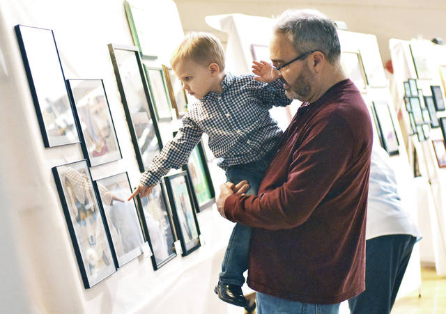 A drawing of a dog catches the eye of William Doolittle, 3, of Piqua, son of Melvin and Caroline Doolittle, while in the arms of his grandfather, Ken Cummings, of Troy. The two were attending Christian Academy Schools' Art From the Heart celebration, Saturday, Feb. 24. People could bid on the art on display. Musical performances the school show choir, Voices Eternal, were enjoyed. Denise McPheron, of Sidney, won a diamond necklace donated by Allison's Custom Jewelry for a raffle during the fundraiser. The art that was auctioned was created by the students at Christian Academy Schools, including William's brother, Jackson.