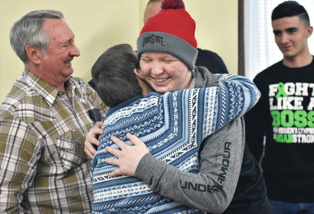 Fairlawn High School student Noah Haynes, third from left, 16, of Sidney, son of Kiley and Jason Swiger and Mitch Haynes, greets family friend Carol Cox, of Rossburg, with a hug during a benefit for Haynes held at the Sidney Temperance Masonic Lodge Saturday, Saturday, Feb. 24. Behind Haynes are, left to right, Stan Cox, of Rossburg, Haynes' grandpa Mitch Haynes and Haynes' brother Bradly Haynes, 17, of Sidney, son of Mitch Haynes and Jackie Harris. Haynes was diagnosed with Burkitt's lymphoma in October of 2017. He has undergone 6 intensive bouts of chemotherapy at Dayton Children's Hospital. Haynes has one last chemotherapy treatment in March. After some CT scans and a PET scan Haynes' doctors will determine the next route for treatment. Kiley Swiger said between 300 and 400 people attended the benefit which had a cake wheel, live music by Terry Zee Fisher, food, and a number of raffles. Anyone who wants to buy a Noah T-shirt, tumbler, wristband or lanyard to help with treatment and transportation costs can call 937-726-1758 or 937-489-9579.