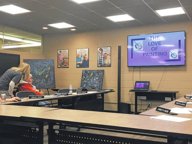 Laura Boice, of St. Marys, receives assistance from Service & Support Administrator Amanda Seigle, talking to the Auglaize Board of DD members about her love of painting.