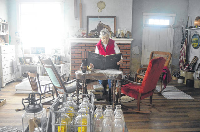 Barb Ditmer looks over historical material that she will display as Shelby County's oldest house becomes a museum. Ditmer owns the home, which is in rural Houston. She raised a family there before constructing a new house at the same farm in 1967.