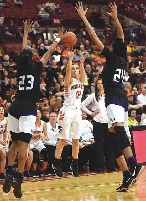 Versailles senior guard Kami McEldowney, center, shoots with pressure from two Africentric defenders during the Division III state championship game on Saturday at the Schottenstein Center in Columbus.