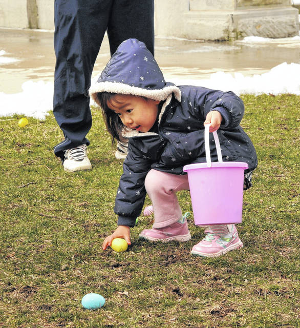 Hinoka Saruyama, 3, daughter of Misauni and Mayumi Saruyama, of Sidney, reaches down to pick up an Easter egg during the hunt Saturday morning on courtsquare in downtown Sidney.