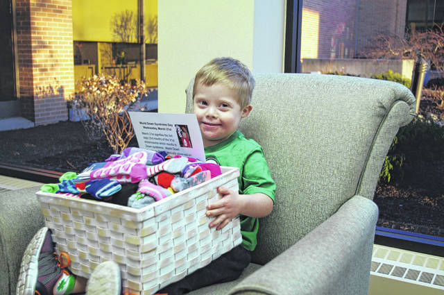 Grant Topp, 4, son of Mary Topp, of St. Marys, holds a basket of crazy socks he will donate to pediatric patients of the Joint Township District Memorial Hospital in St. Marys to commemorate World Down Syndrome Day, March 21.