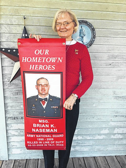 Diane Naseman holds the banner which honors her son, Brian K. Naseman, who was killed in 2009 in Taji, Iraq, while serving in the Army National Guard.