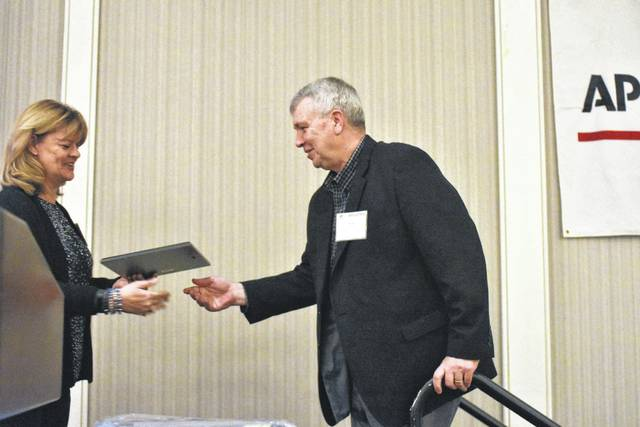 Ohio Associated Press Media Editor President Julie Wallace presents retired Sidney Daily News Sports Editor Ken Barhorst with his Hall of Fame award Saturday in Columbus.
