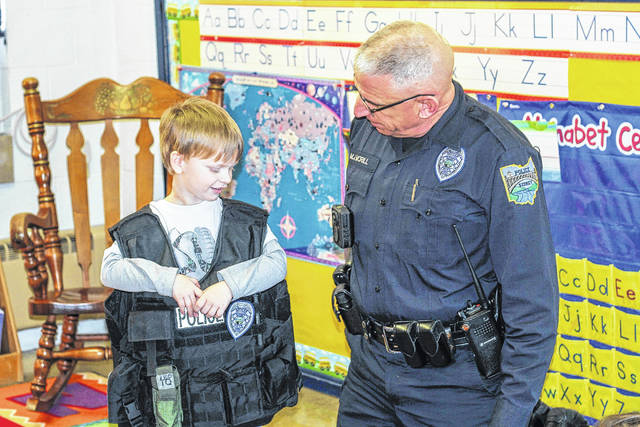 """Hudson Winemiller, 4, son of Brian and Molly Winemiller, of Sidney, tries on a police officer's vest as Sidney Police Officer Mike McRill watches. McRill visited the Sidney Cooperative Nursery School on Police Day. The students were learning about the letter """"P."""""""