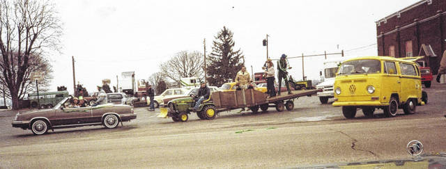 Floats in the annual McCartyville St. Patrick's Day parade have changed over the years and so have their power sources. At top, a tractor pulls a flatbed float in the inaugural parade in 1984. At bottom, an award-winning float from a more recent parade gets into line in front of a semi that pulls another, unseen float. The 2018 parade will step off at 1:30 p.m., March 17, in downtown McCartyville.