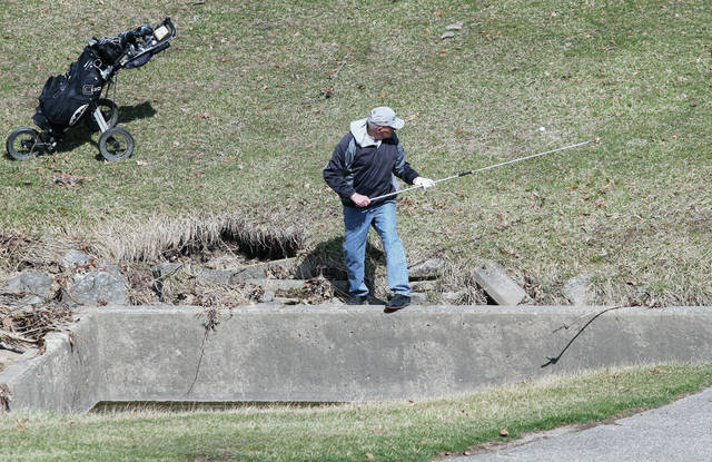 Don Fair, of Sidney, uses a telescoping pole to retrieve his golf ball from a water hazard at the Moose golf course Tuesday, March 6. Fair was golfing with his longtime golfing partner Darrell Spangler. The two men have already golfed twice this winter starting in early December. It was around 50 degrees while the men golfed Tuesday.