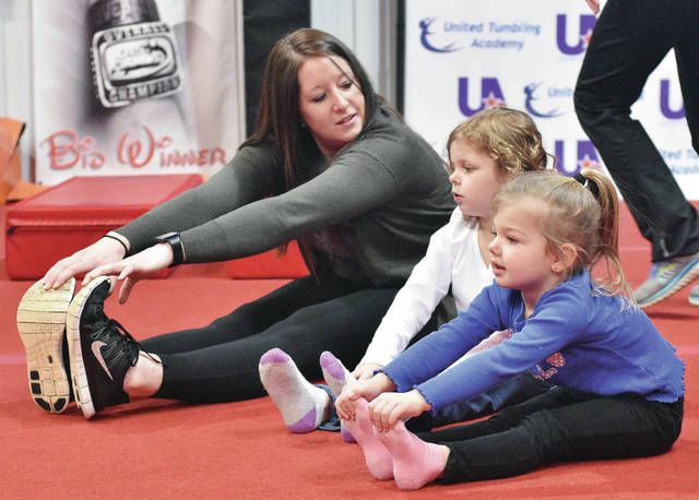 United Tumbing Academy owner, Abbey Kramer, left to right, of Shawnee, helps Sidney Cooperative Nursery School students Myleigh Fitchpatrick, 4, ward of Lance and Joyce Mitchell, and Rosalina Sherman, 3, both of Sidney, daughter of Cody and Felicia Sherman, stretch before doing some gymnastics. The Sidney Cooperative Nursery School students came to the United Tumbing Academy on a field trip Wednesday, March 7.