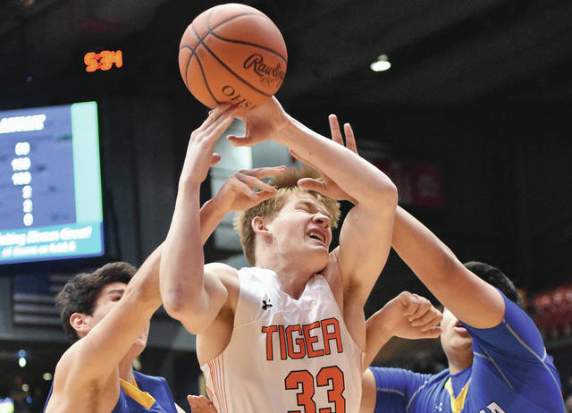 Versailles' AJ Ahrens shoots as Madeira's Mark Manfredi, left, and Eric Hoeffel defend during a Division III district final at UD Arena on Wednesday. Ahrens led the Tigers with 15 points.