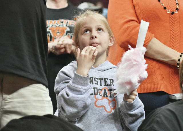 Avery Woehrmyer, 7, of Minster, daughter of Jon and Julie Woehrmyer, munches on cotten candy as she watches the Minster Wildcats take the floor against the Waterford Wildcats in a Division lV State Semifinal game at the Schottenstein Center in Columbus Thursday, March 15. The final score was Minster 46 Waterford 31.